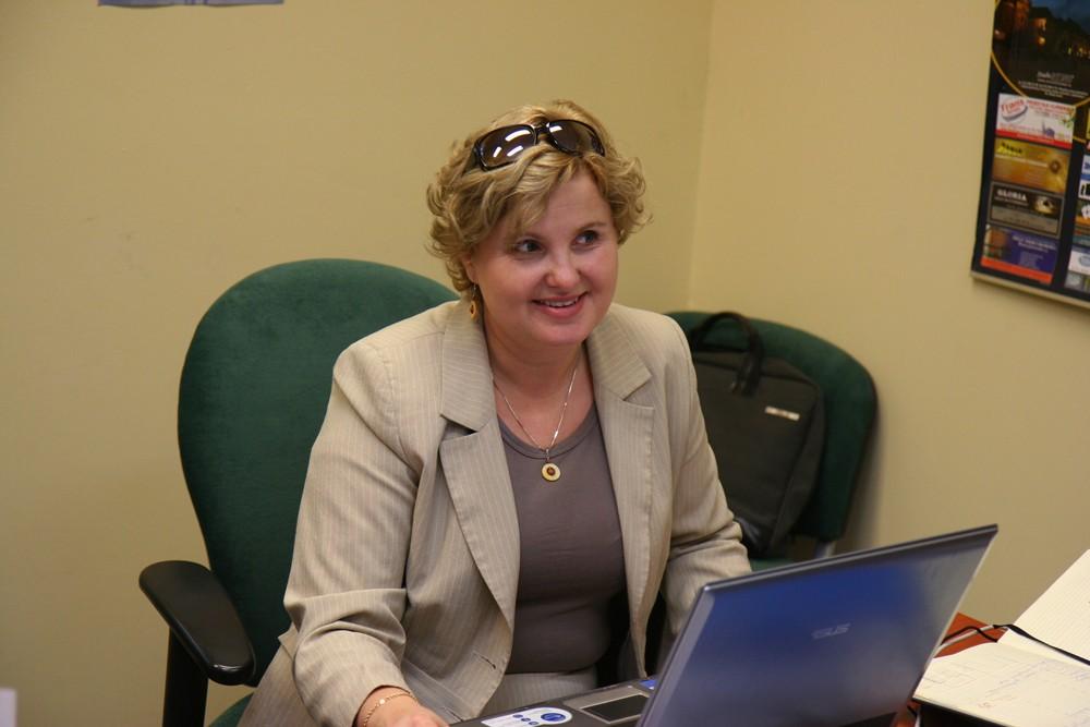 Uśmiechnięta Pani Dyrektor WZAZ Ewa Wójcik, która siedzi za biurkiem ma przed sobą otwartego laptopa