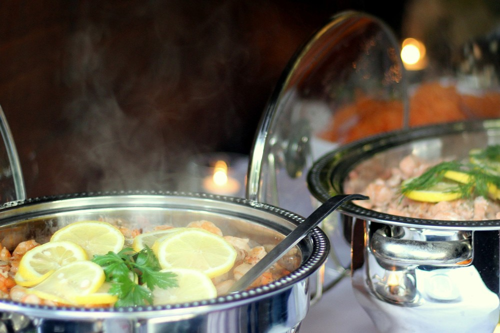 srebrny garnek z potrawą gorącą obłożony plastrami cytryny