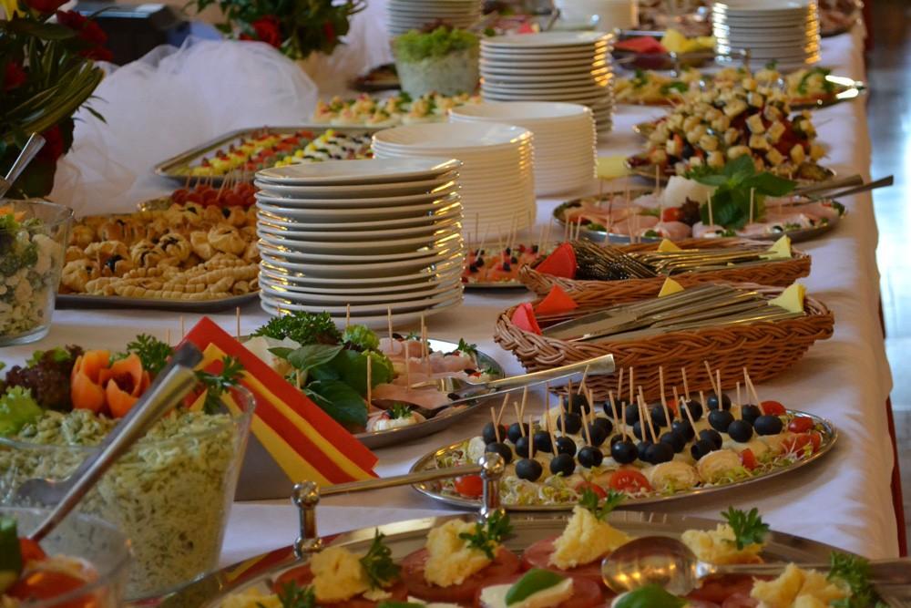 długi stół zastawiony przekąskami słodkimi sałatkami koreczkami z łososia i tortillą