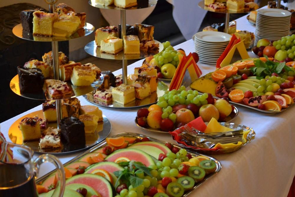stół zastawiony paterami z ciastem różnego rodzaju z tacami owoców